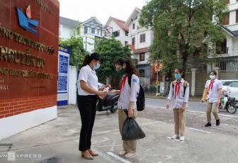 A teacher is present in front of the Nguyen Du Middle School in Hanois Nam Tu Liem District to greet students and have their hands sanitized on Monday morning. Students and teachers all wear masks and distance from each other for at least a meter to prevent infection.