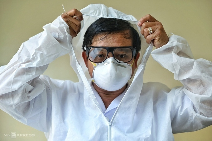 Doctor Nguyen Thanh Phong, Head of the Infectious Disease Department at HCMC Hospital for Tropical Diseases, puts on protective clothing before entering treatment area for Covid-19 patients, March 11, 2020. Photo by VnExpress/Huu Khoa.