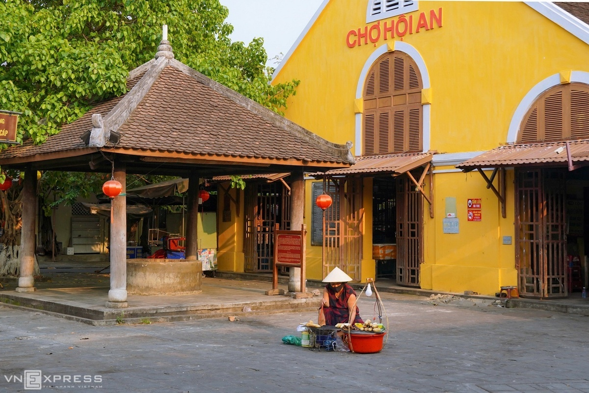 A woman wearing a mask with a basket of grilled corn sits at the deserted Hoi An market. The picture was taken on April 6, when the country was in the social distancing campaign to contain the spread of Covid-19 pandemic.