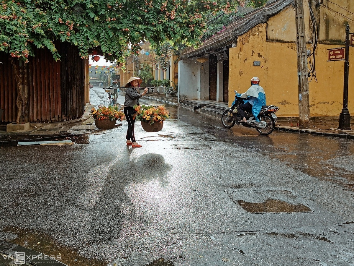 A woman carrying a basket of flowers walk under the rain at the crossroad of Hoang Van Thu and Nguyen Thai Hoc Streets.