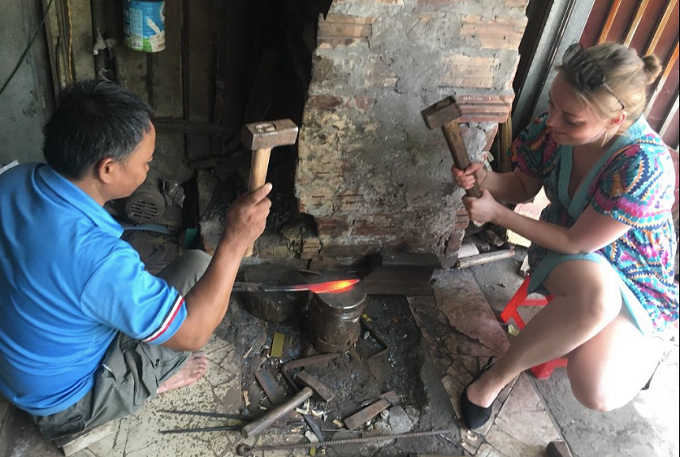Hanoian blacksmith Hoang Van Chinh trains Hasley from Sheffield, the UK to use the hammer to shape the knife in his workshop in Da Sy Village, Ha Dong District in Hanoi. Photo VnExpress.