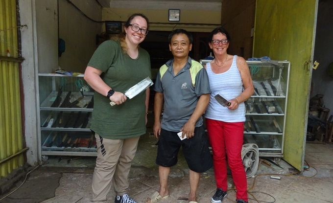 Hanah from Roslin, the U.K. (L) and her mother pose for a photo with Chinh in front of the backsmiths house, with the knives they forged on their own. Photo by VnExpress