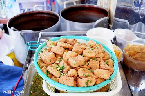 Crispy fried tofu marinated with onion sauce is a typical feature of the dish.