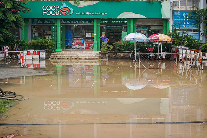 Flood water in front of a convenience store. Businesses on both sides of the road worry about slow business due to the unfinished construction road.